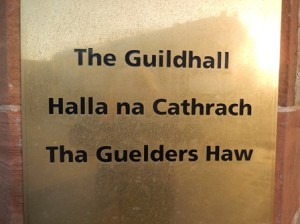 Sign on the Guidlhall in Derry in three langagues: English, Irish Gaelic, Ulster Scots name in three langagues