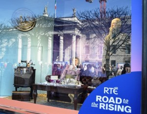 "Shop window depicting George Bernard Shaw and reflecting the General Post office and crowds assembling for RTE's ""Road to the Rising"""